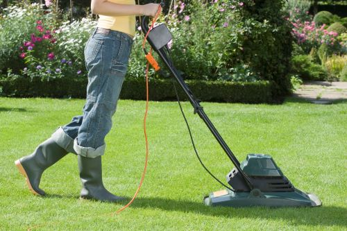 woman pushing quiet electric lawn mower