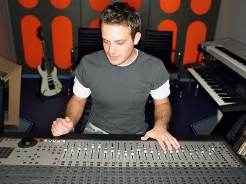 guy at a sound board in a recording studio