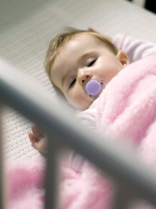baby sleeping in nursery in crib