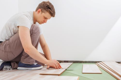 man cutting underlayment for laminate floor