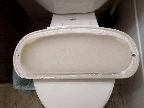 Toilet Tank Lid with Deposits Around Edge