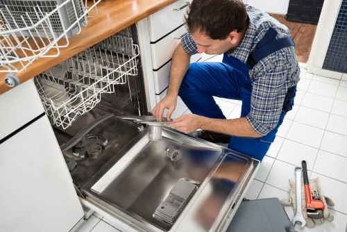 Technician soundproofing a dishwasher