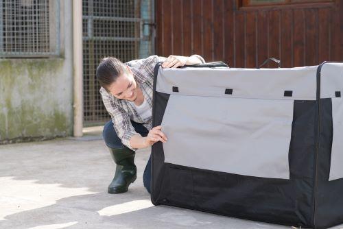 woman peeking in through dog crate cover