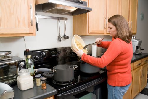 woman cooking under range hood