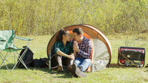 Man and woman camping in a tent with a generator sitting outside