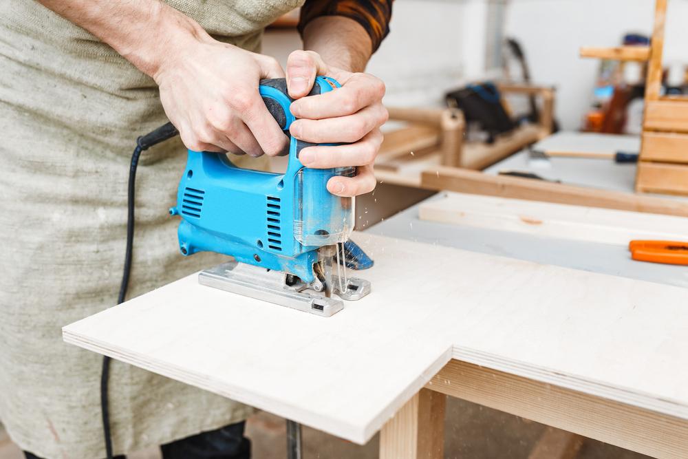 Man cutting board with a quiet jigsaw