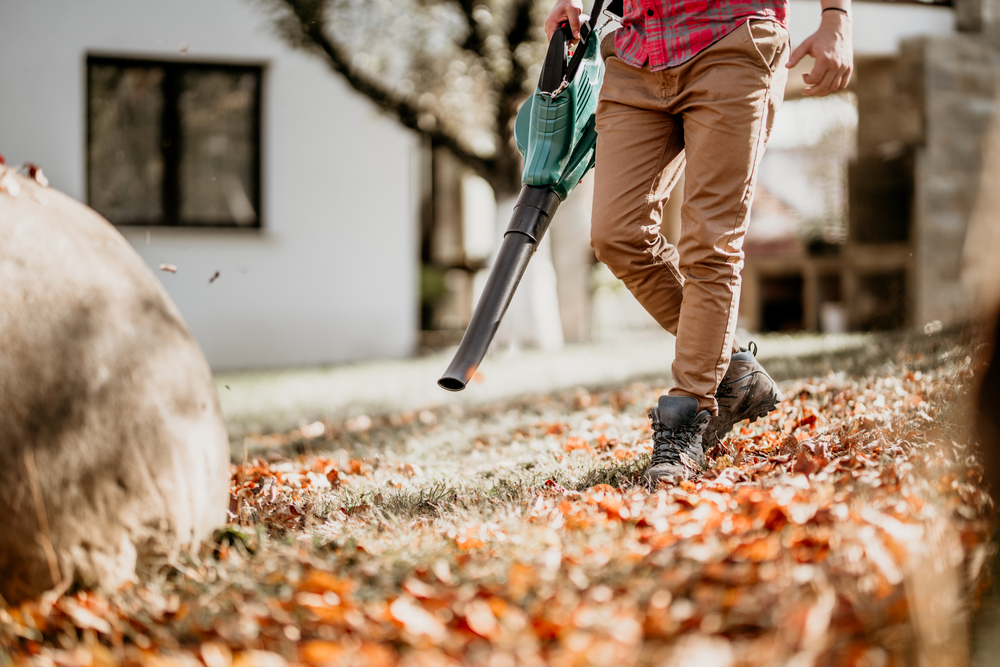 Man blowing leaves in front of house with quiet leaf blower