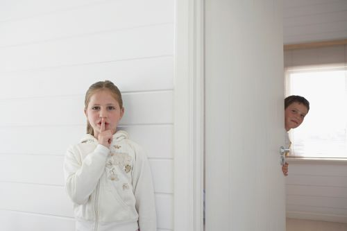 boy and girl opening a door quietly