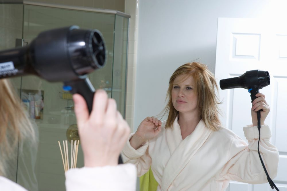 woman blow drying hair with hair dryer in bathroom